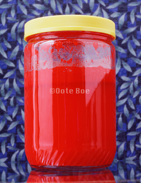 red fluid in glass jar with yellow lid against blue background