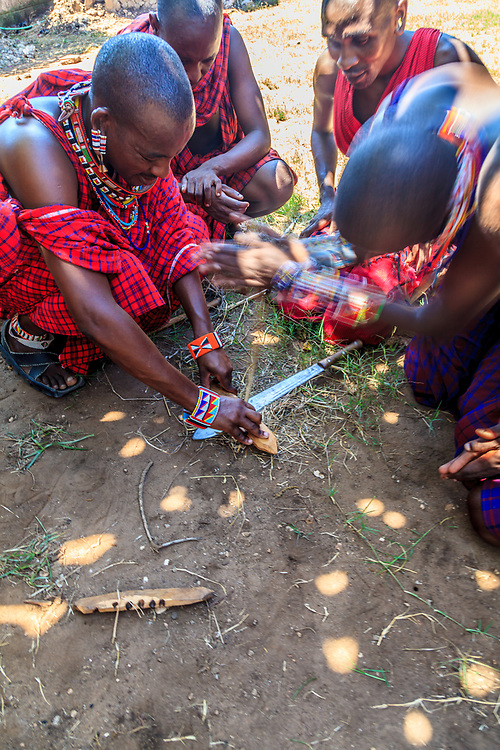 The Maasai tribesmen show how they make fire by rotating a wood stick in a hole in a board in Kenya.