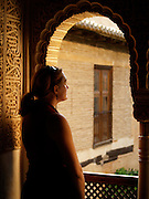 A woman gazes out of a window inside the Palacios Nazaries, The Alhambra, Granada (Andalusia), Spain.