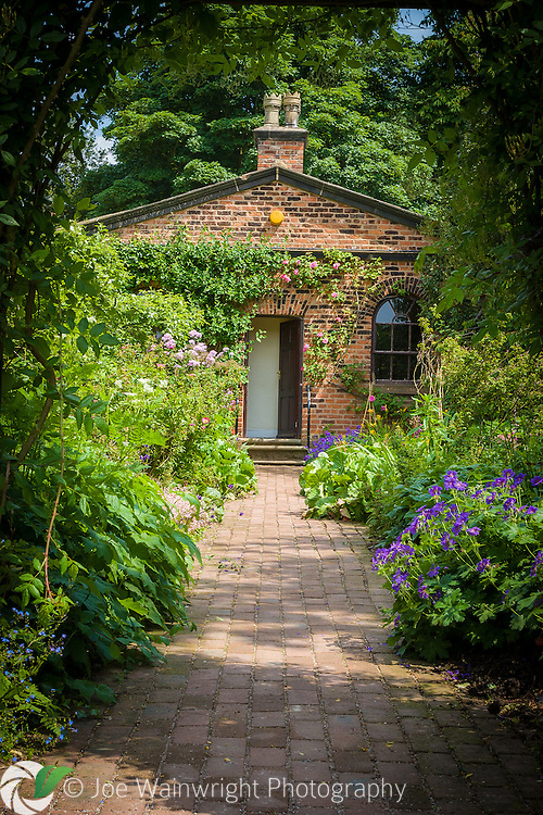 A path, lined with perennials including geraniums, leads to the rose-clad Gardener's Cottage in the Walled garden at Norton Priory, Runcorn, Cheshire.