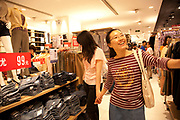 Shoppers inside the Uniqlo store in Joy City shopping Mall. Xidan is one of the main commercial shopping area in the Xicheng district of Beijing, China. With Joy City as it's centerpiece, a 13-story complex of western and Chinese shops. This is a shoppers haven as modern consumerism and commerce have a strong grip on Beijing's shop hungry crowds.