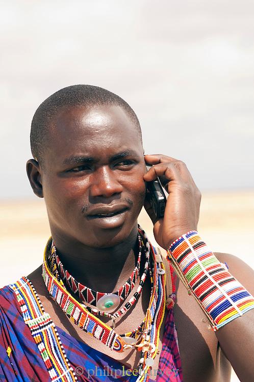 Maasai tribesman talking on cell phone, Amboseli National Park, Kenya