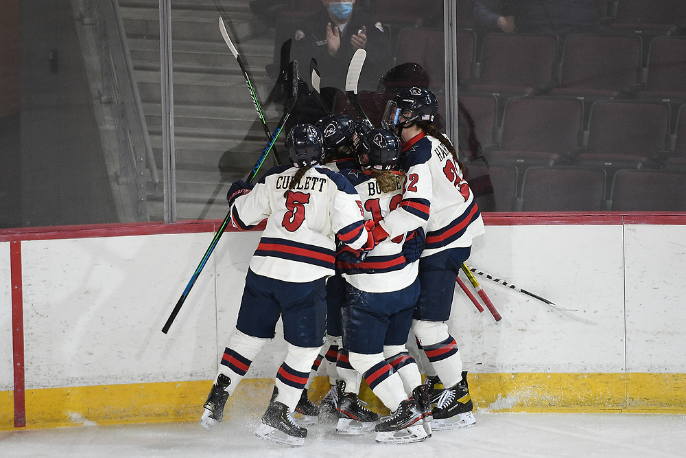 ERIE, PA - MARCH 04: Maggy Burbidge #9 of the Robert Morris Colonials is mobbed by her teammates after scoring a goal in the first period during the game against the RIT Tigers at the Erie Insurance Arena on March 4, 2021 in Erie, Pennsylvania. (Photo by Justin Berl/Robert Morris Athletics)