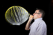 This image is part of a sequence where a man over inflates a balloon until it burst.  The image was taken with a high speed flash system. The motion is effectively frozen in time due to the short duration of the flash (1/20,000 th of a second). The balloon was filled with a few milliliters of water before it was inflated. When the balloon is popped, the gas quickly expands and cools. This cooling converts the water vapor in the balloon into suspended water droplets which can be seen as a cloud.