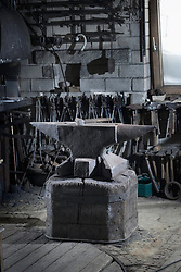 Hammer lying on an iron anvil in a traditional blacksmith forge, Bavaria, Germany