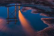 Roadside rain puddle reflects power poles and smoke stacks, night light, Nippon Paper Industries, Clallam County, Port Angeles, Washingtion, USA