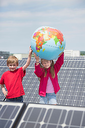 Young kids brother sister holding globe