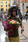A man in a motorcycle helmet and keys about to deliver a bunch of flowers, Verona, Italy