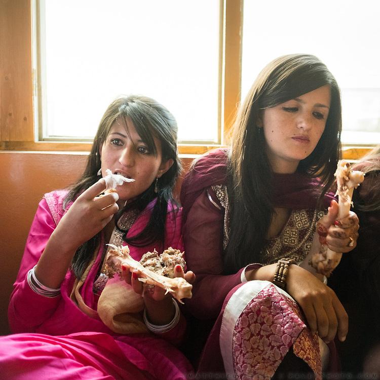 Girls eating mutton off the bone. Mehnaz's love marriage celebration in Zood Khun, Chapursan valley.