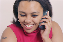 Woman with tattoo using mobile phone smiling,