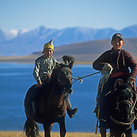 Youngster ride their horses beside a lake in the Darhad Valley of northern Mongolia