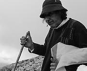 A pilgrim smokes a cigarette as he makes his way up the mountain.