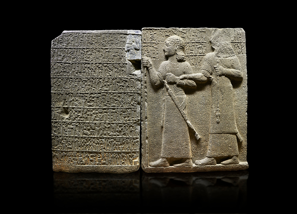 """Hittite monumental relief sculpted orthostat stone panel of Royal Buttress. Basalt, Karkamıs, (Kargamıs), Carchemish (Karkemish), 900-700 B.C. Anatolian Civilisations Museum, Ankara, Turkey.<br /> <br /> Hieroglyph panel (left) - Discourse of Yariris. Yariris presents his predecessor, the eldest son Kamanis, to his people. <br /> Right Panel - King Araras holds his son Kamanis from the wrist. King carries a sceptre in his hand and a sword at his waist while the prince leans on a stick and carries a sword on his shoulder. <br /> <br /> Hieroglyphs reads; """"This is Kamanis and his siblings.) held his hand and despite the fact that he is a child, I located him on the temple. This is Yariris' image"""".  <br /> <br /> Against a black background. .<br />  <br /> If you prefer to buy from our ALAMY STOCK LIBRARY page at https://www.alamy.com/portfolio/paul-williams-funkystock/hittite-art-antiquities.html  - Type  Karkamıs in LOWER SEARCH WITHIN GALLERY box. Refine search by adding background colour, place, museum etc.<br /> <br /> Visit our HITTITE PHOTO COLLECTIONS for more photos to download or buy as wall art prints https://funkystock.photoshelter.com/gallery-collection/The-Hittites-Art-Artefacts-Antiquities-Historic-Sites-Pictures-Images-of/C0000NUBSMhSc3Oo"""