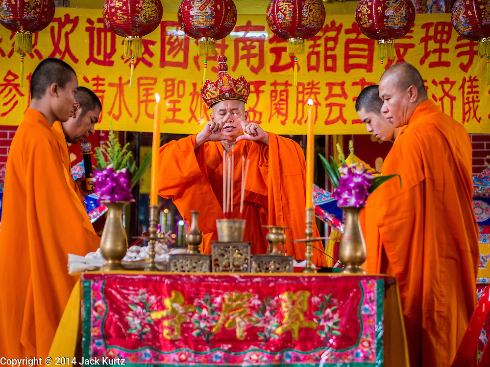 """09 AUGUST 2014 - BANGKOK, THAILAND:     Vietnamese Buddhist monks lead a service for Ghost Month at the Ruby Goddess Shrine in the Dusit section of Bangkok. The seventh month of the Chinese Lunar calendar is called """"Ghost Month"""" during which ghosts and spirits, including those of the deceased ancestors, come out from the lower realm. It is common for Chinese people to make merit during the month by burning """"hell money"""" and presenting food to the ghosts. At Chinese temples in Thailand, it is also customary to give food to the poorer people in the community.    PHOTO BY JACK KURTZ"""