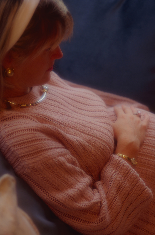 Contemplative pregnant woman, pink sweater