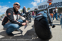 Harley-Davidson's Paul James judges the open custom class of the Ride-In Show at the Harley-Davidson display Wednesday during Daytona Bike Week. FL, USA. March 12, 2014.  Photography ©2014 Michael Lichter.