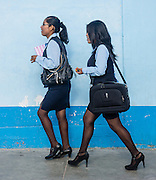 Uniformed working women walk a street in Yungay, in the Andes Mountains,  Ancash Region, Peru, South America