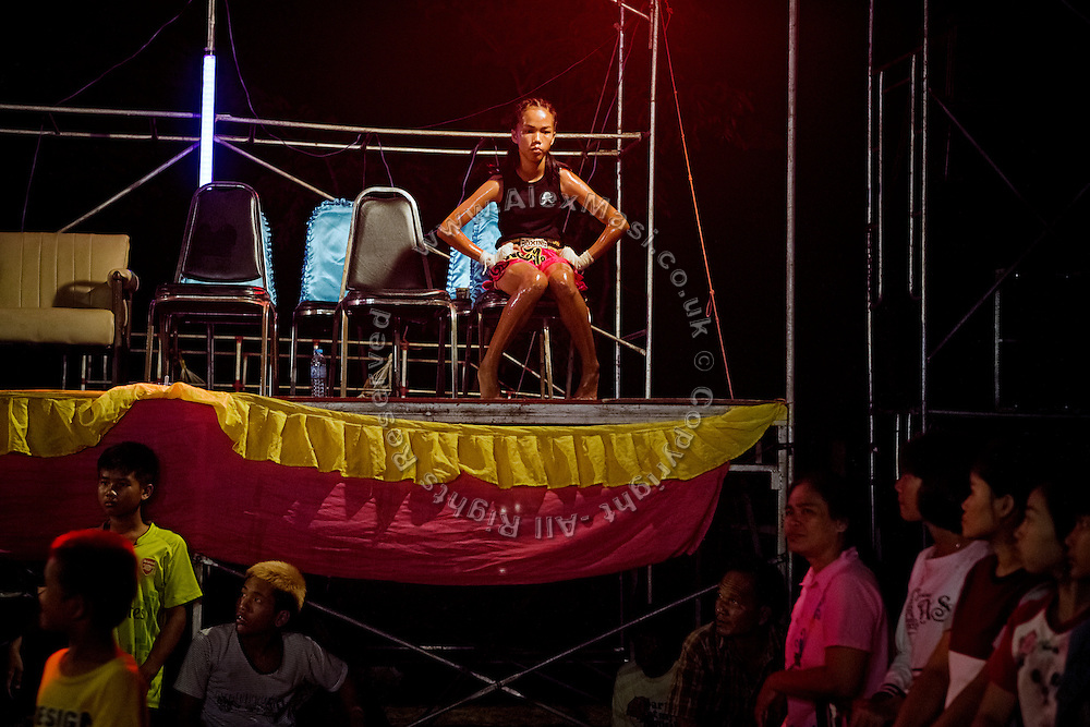 An adolescent girl is sitting on the stage, awaiting the start of her Muay Thai boxing match, in a small arena set up in a village near Ubon Ratchathani, northeast Thailand.