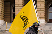 """02 JANUARY 2021 - DES MOINES, IOWA: A man carries a Gadsden Flag around the Iowa State Capitol. About 30 people marched around the Iowa State Capitol Saturday afternoon to protest the outcome of the November 3 general election in the United States. They are a part of the """"Stop the Steal"""" movement which maintains that the election was stolen from Donald Trump by massive voter fraud. There is no evidence supporting their conspiracy theory. This is the 9th week Donald Trump supporters have marched around the Capitol. They've been there every week since the Nov. 3 election. More than 1,000 people showed up the first week, but the crowd has gotten smaller every week.    PHOTO BY JACK KURTZ"""
