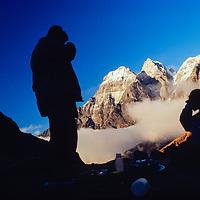 Trekkers camp atop a ridge Mt. Ama Dablam towers over Pheriche village in the Khumbu region of Nepal. 1980.