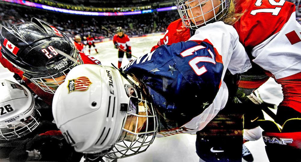 !!!!! JUISTE VERSIE !!!!!<br /> Rusland, Sochi, 20-02-2014.<br /> Olympische Winterspelen, IJshockey, Vrouwen, Finale.<br /> Canada - USA  : 3-2  in extra time.<br /> Hilary Knight van de USA wordt tegen de boarding gewerkt door de canadese vrouwn Marie-Philip Poulin ( nr 29 ) en Meaghan Mikkelson ( rechts met nr 12 ).<br /> De Canadese vrouwen worden na een spectaculaire inhaalrce na een 0-2 achtestand in de overtime alsnog olympisch kampioen.<br /> Foto: Klaas Jan van der Weij