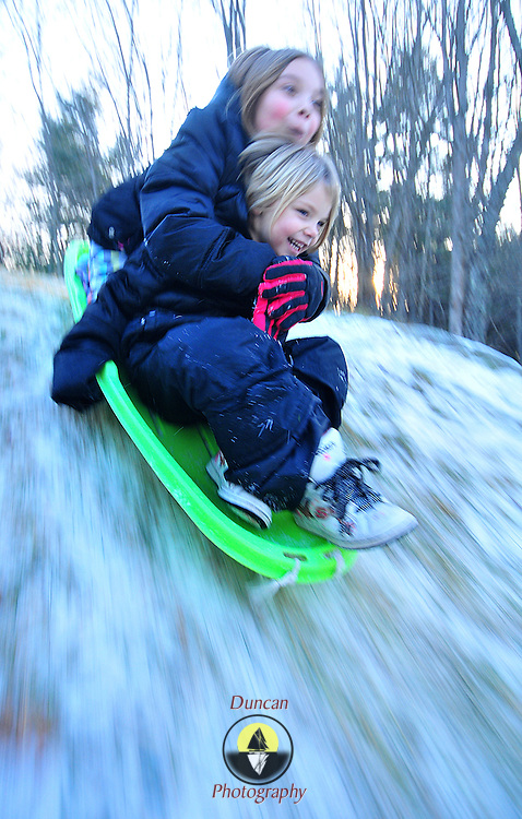 12/11/10  - BATH, Maine. -- Paige Bishop, 8, rides on the back of the sled -- and her sister Haylee, 4, on a small hill near their home in Bath on Saturday afternoon. Temps plummeted at the end of last week, leaving a dusting of sleddable snow. Rain through the weekend wiped out the girls' sled hill over the weekend -- and they are likely out of luck through next Tuesday -- when light snow showers are predicted again. Photo by Roger S. Duncan.