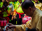 16 FEBRUARY 2018 - BANGKOK, THAILAND:  A man lights candles as a blessing at the Canton Shrine during Chinese New Year celebrations in the Chinatown neighborhood of Bangkok. Thailand has a large Chinese community and Lunar New Year is widely celebrated, especially in larger cities. This will be the Year of the Dog.      PHOTO BY JACK KURTZ