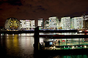 Night scene looking over the River Thames towards the skyline of More London area offices and business district. This area is a recent development which is now thriving and bustling with more buildings being constructed in this moderm glass style and filling the area with office workers. In the foreground is the Thames Clipper stop at Tower Millennium Pier
