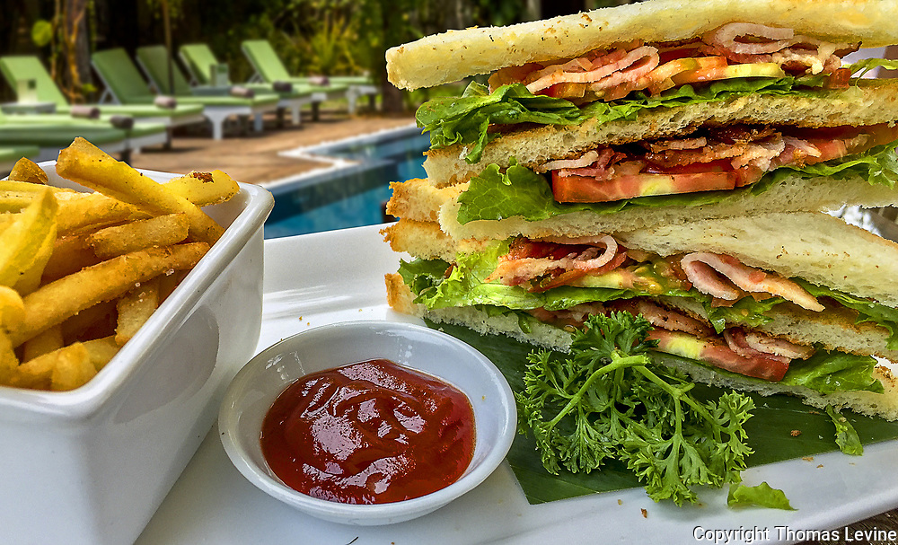 Club sandwich dining next to a pool at a resort in Asia. Background consists of a swimming pool with green lounge chairs. (iPhone)