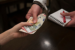 Woman paying paper notes at restaurant