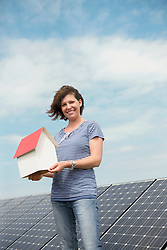 Photovoltaic panel woman holding model house
