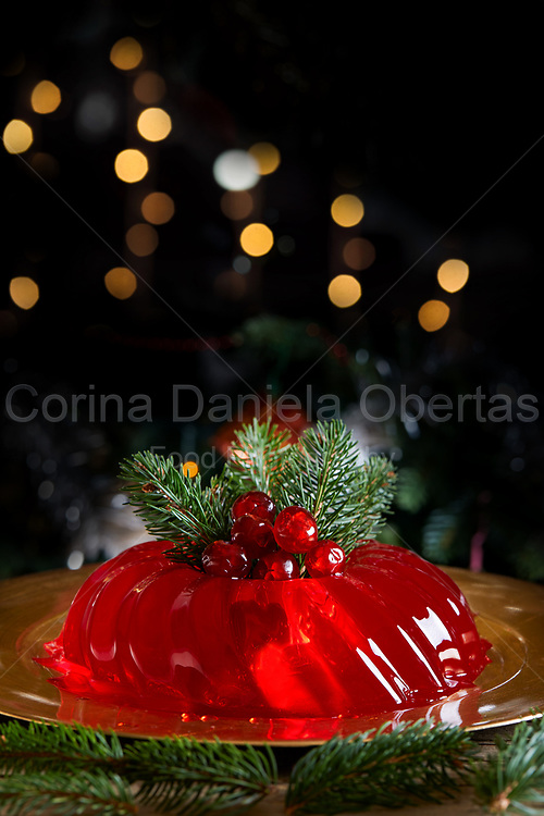 Red jelly decorated for Christmas with fir branches and candied cherries, on dark background with bokeh lights.
