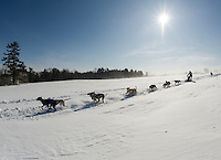High winds blowing the fresh snow gave a fresh track for Doug Butler and his dog team of Bristol, VT during the final day of Open Class racing at the 86th annual Laconia World Championship Sled Dog Races on Sunday afternoon.  (Karen Bobotas/for the Laconia Daily Sun)