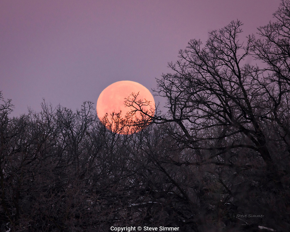 """This is a so-called """"Supermoon"""" because it is a bit closer to the earth on this day. It is about 15% larger than an ordinary full moon. The purple sky is caused by the rising sun, which was directly behind me as I took this photo."""