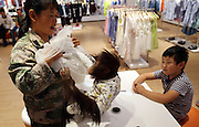 """KUNMING, CHINA - AUGUST 24: Famous red hair orangutan \""""Er Mao\"""" of Yunnan Wild Animals Park wears new clothes at a shopping mall on August 24, 2016 in Kunming, Yunnan Province of China. Famous red hair orangutan \""""Er Mao\"""" of Yunnan Wild Animals Park tried new clothes and finally bought three skirts with the help of its keeper at the children\'s wear store in a shopping mall on Wednesday in Kunming. <br /> ©Exclusivepix Media"""