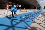 A woman cycles along the dedicated cycle path that travels alongside the elevated section of the A13 Newham Way in Canning Town in the East End, on 11th August 2021, in London, England.