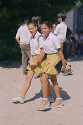 Secondary school girls walking together in playground wearing uniform,