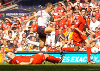 Photo: Henry Browne.<br /> Wales v England. FIFA World Cup Qualifying match.<br /> 03/09/2005.<br /> Joe Cole of England skips over a challenge from Robert Page of Wales.