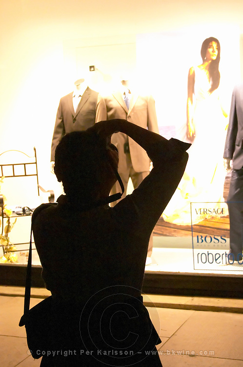 A black silhouette of a photographer taking a picture at night of a clothes fashion shop (Versace, Boss, Roberto marked in the widow) window display on the Cours de l'Intendence  city  Bordeaux Gironde Aquitaine France