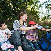 Afternoon, Monday 14th of September 2015. Aysha just crossed into Hungary and she has a little rest under the trees before going to a field where buses are waiting to take the refugees to the Austrian border. A Syrian teenager who was carrying Sham during the long march on the rail line, is giving her 2 cans of condensed milk that was given to him in Greece by volunteers.