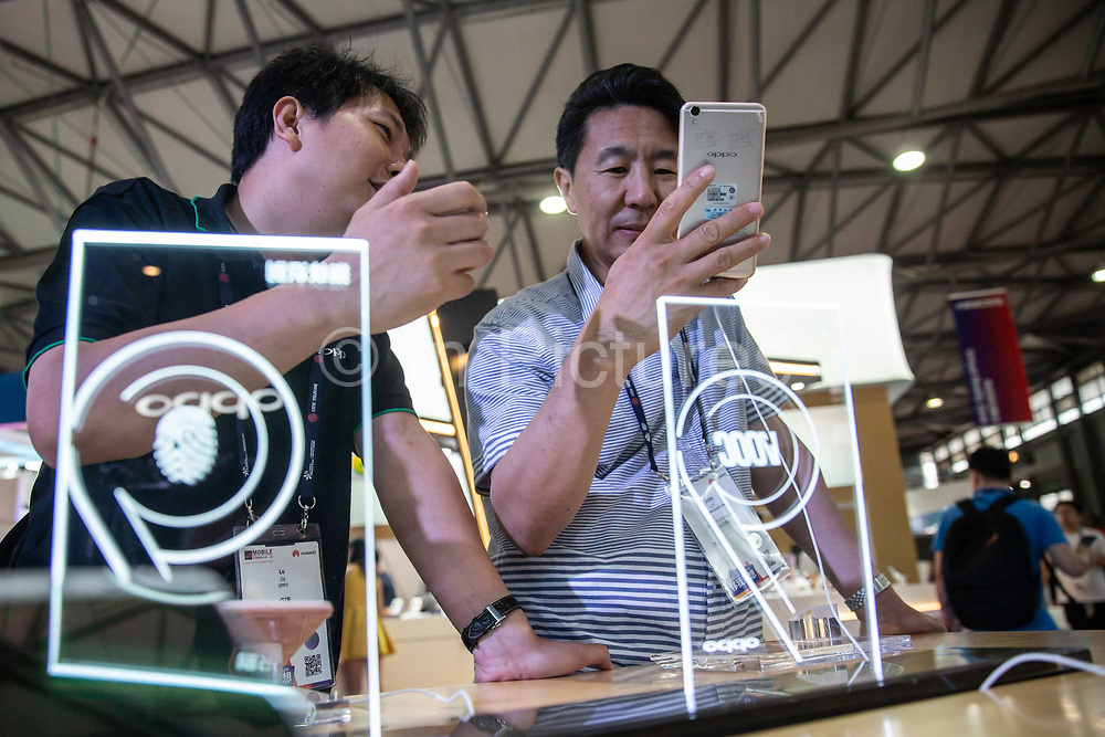 Attendees look at OPPO smartphones on display at the Mobile World Congress Shanghai in Shanghai, China, on Wednesday, June 29, 2016.