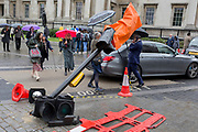 During seasonal spring rain, pedestrians cross Trafalgar Square and around the leaning traffic light post, damaged after a recent vehicle crash, on 9th May 2019, in London, England.