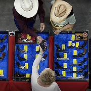 Show attendees shop for handguns at the Western Collectibles & Firearms Gun Show held in Tim's Toyota Center. Guns are big business in Arizona, which has more than 1,200 federally licensed firearm dealers that sell more than 200,000 guns a year and is on track to set a gun-sales record this year. The Bureau of Alcohol, Tobacco, Firearms and Explosives licenses more than 100 Arizona-based makers of guns and gun parts that employ more than 1,000 people.