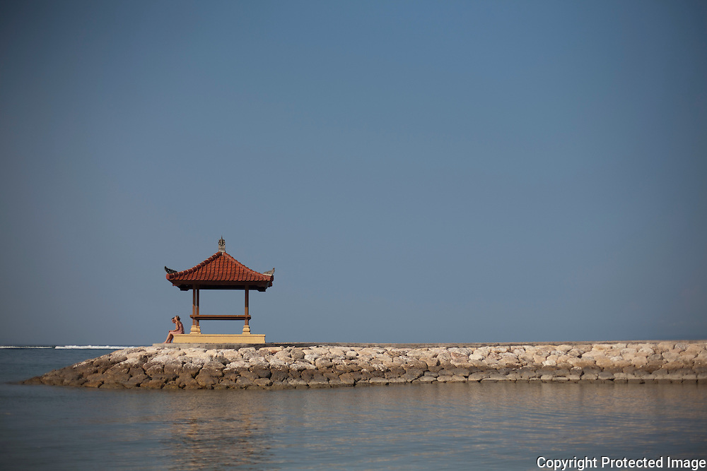A couple rest on a pavilion near the beach in Sanur on the island of Bali, Indonesia.