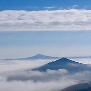 Volcano tops in low-hanging clouds,  Auvergne, Frankrijk