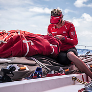Leg 02, Lisbon to Cape Town, day 05, on board MAPFRE, Sophie Ciszek fixing a bag on the bow. Photo by Ugo Fonolla/Volvo Ocean Race. 09 November, 2017.