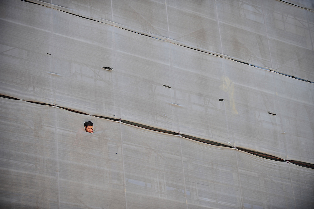 A men peaks, through the covers of a building under construction, at the march in the memory of the Romanian gipsy Holocaust.