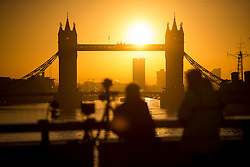 © Licensed to London News Pictures. 16/02/2016. London, UK. Photographers gather on London Bridge to watch the sun rise behind Tower Bridge in central London on a cold winter morning. Temperatures in the capital dropped below zero last night. Photo credit: Ben Cawthra/LNP
