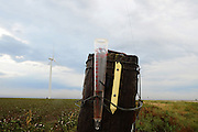 A rain gauge wired to a fencepost is partially filled after a couple of brief showers in the Texas panhandle north of Amarillo.<br /> <br /> ©2013 Robert W. Hart