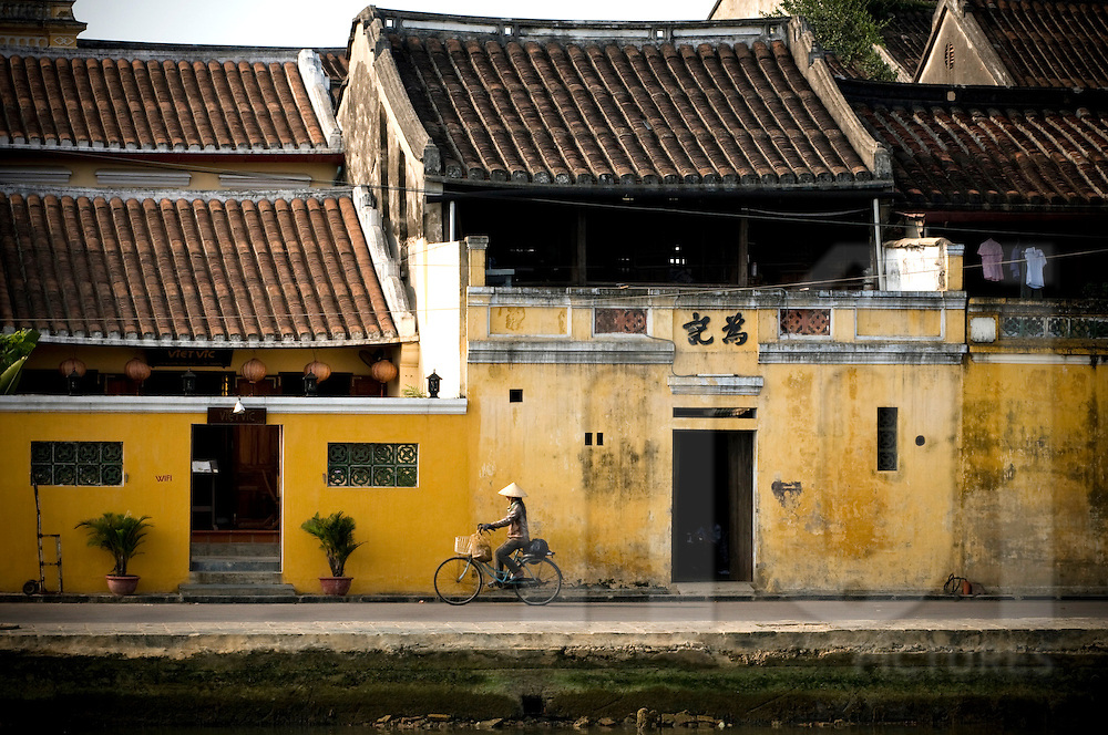A Vietnamese woman rides her bicycle through ancient Hoi An past traditional buildings beside Thu Bon River, Vietnam, Southeast Asia